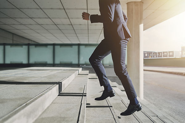 Businessman running fast upstairs. Horizontal outdoors shot..jpg