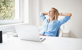 beautiful business woman is relaxing in her homeoffice behind her notebook during corona t