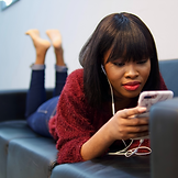 Image of girl lying frontwards on a sofa, watching something on a cellphone with earphones.