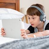 Image of boy leaning on a bed, wearing headphones and watching something on a tablet.