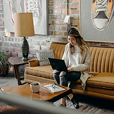 Picture of a woman on her laptop in a room with a brick wall and mustard/brown tone décor.
