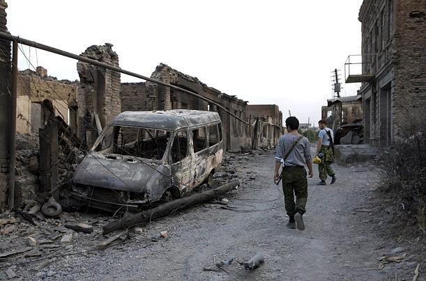 Voluntarios de Ossetia caminan junto a una camioneta incendiada en una calle en Tskhinvali. (Foto: TIME)
