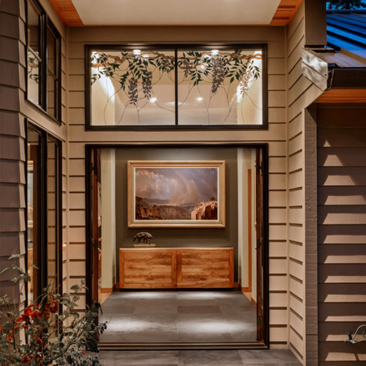 Camano Residence entry with stone paving, double french doors, cove lighting and grey accent wall - Pelletier + Schaar