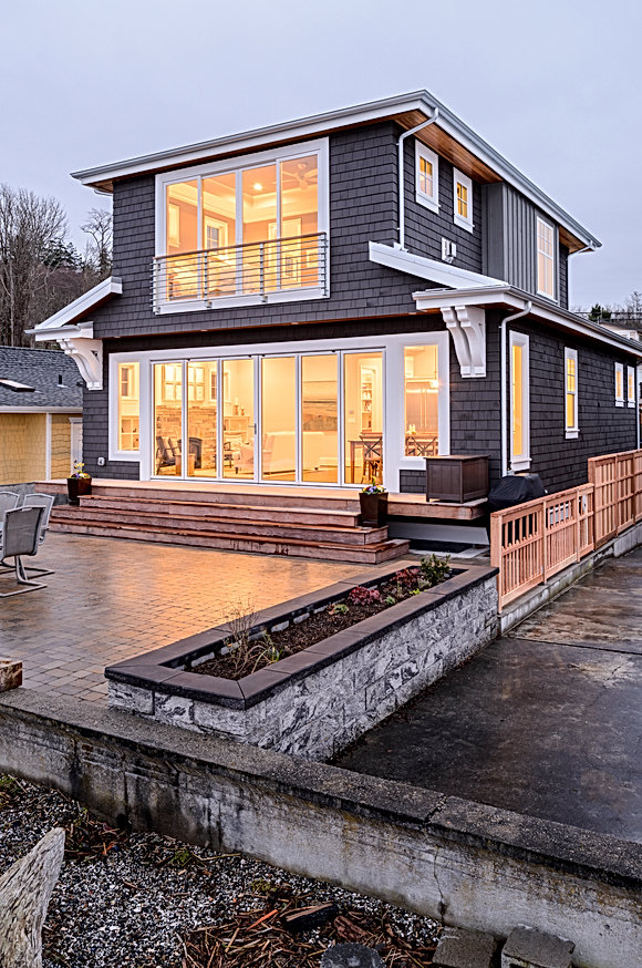 O'Neill Residence beach side glows at dusk with Nana doors connecting with the outdoors - Pelletier + Schaar