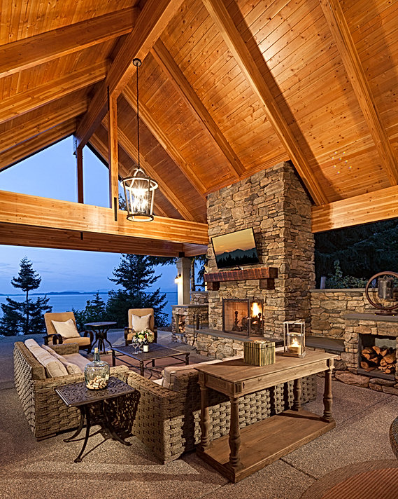 Outdoor living room with stone fireplace and wood beamed ceiling - Pelletier + Schaar