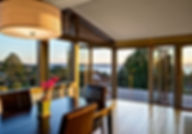 Smith Addition & Deck dining room's Nana doors open to deck and views - Pelletier + Schaar