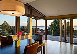 Smith Addition & Deck dining room's Nana doors open to deck and views - Pelletier + Schaar