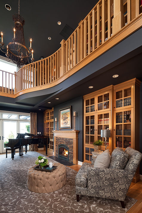 Black two story library with wood balcony and shelves, stone fireplace - Pelletier + Schaar