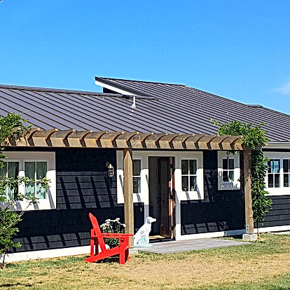 Morelli Cottage entry with trellis, dark shingles, cream trim, shed roof and red chair - Pelletier + Schaar
