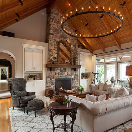 Vaulted living room with wood beamed ceiling, stone fireplace, white cabinets and black chandelier - Pelletier + Schaar