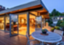 Smith Addition & Deck mid-century modern deck and glass great room glow at dusk - Pelletier + Schaar