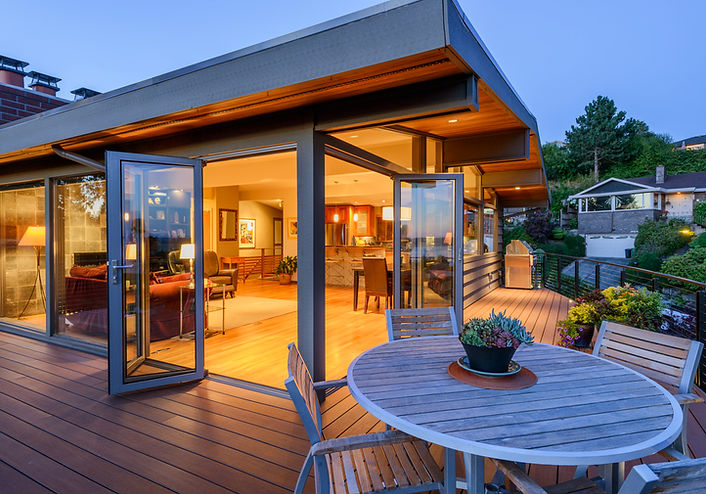 Smith Addition & Deck mid-century modern deck and glass great room glow at dusk - Pelletier + Schaar