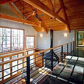 Bomgardner Residence balcony overlooking great room with fireplace and wood trusses- Pelletier + Schaar