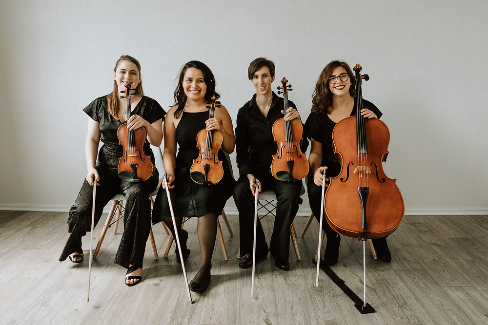 Boom Island String Quartet members posing for a photo in their studio