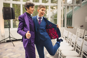 Two brides posing in suits.