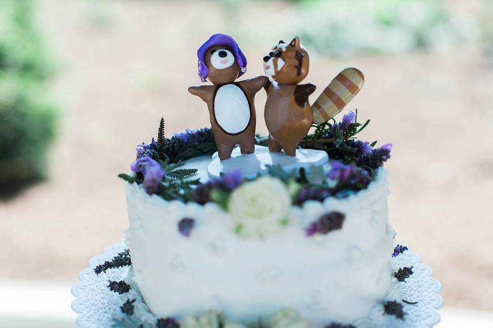 clay wedding cake topper with a red panda and a brown bear as bride and groom