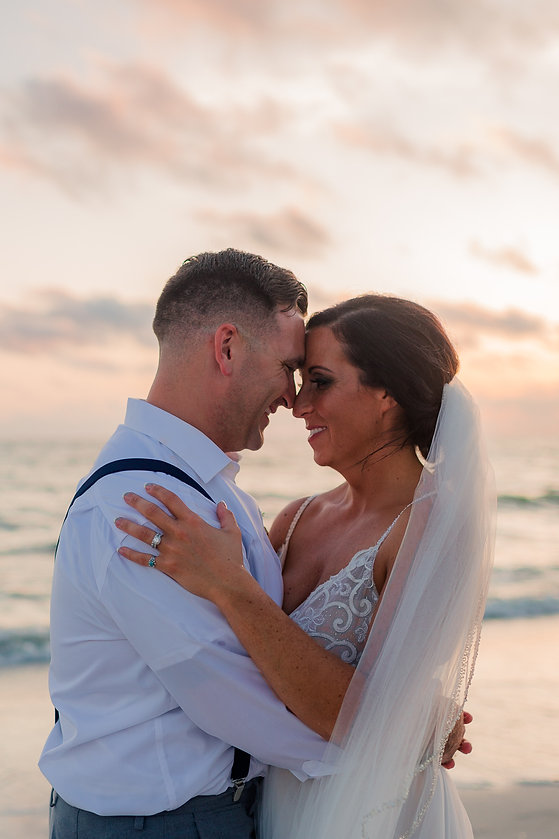 Bride and Groom posing in the sunset at their beach wedding.