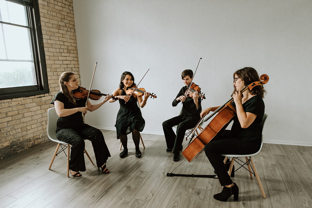 wedding string quartet with two violins, a viola, and a cello rehearsing in their studio