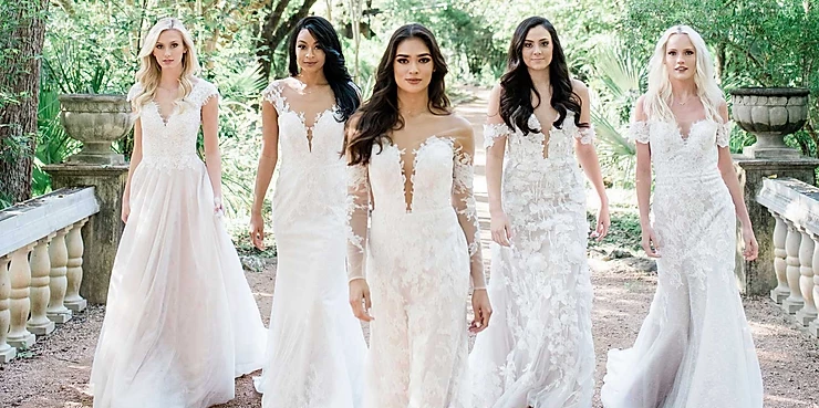 Five bridal models walking on a stone bridge.