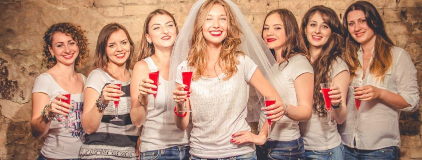 Bride and bridesmaids posing at bachelorette party with cocktails in hand.