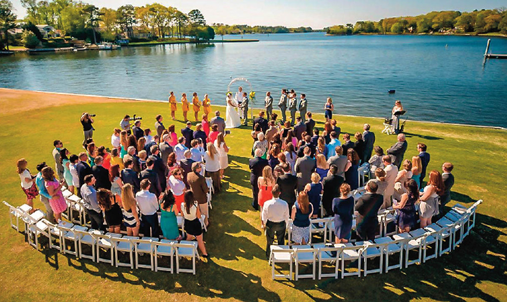 outdoor wedding ceremony by a lake with quarter round seating layout