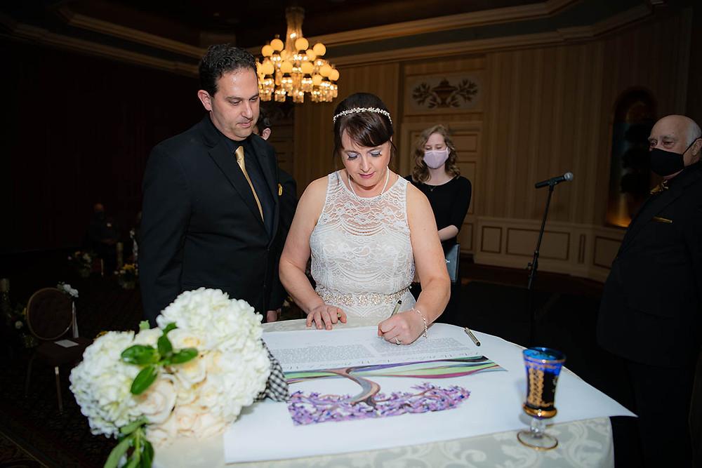 Bride and Groom signing Ketubah.
