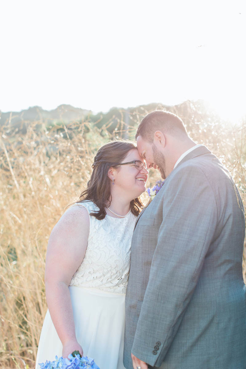 bride and groom with foreheads together at sunset