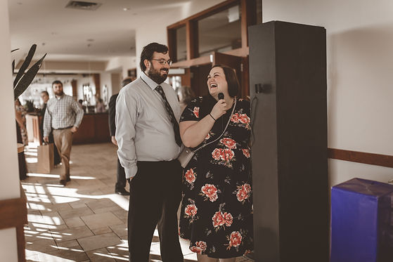 Two wedding guests laughing while recording a message on Woodland Events' video guestbook.