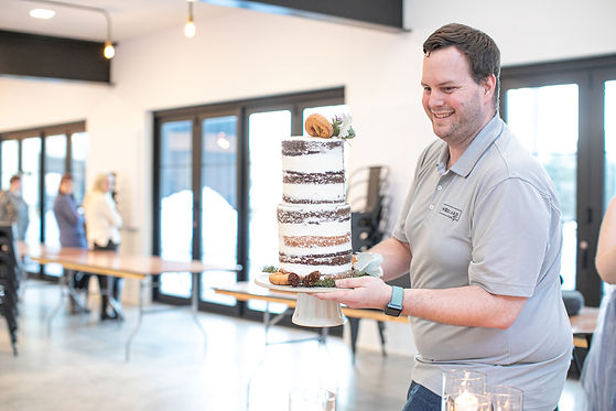 Minnesota wedding planners carrying naked tiered cake with donuts at Pinewood Weddings and Events in Cambridge, Minnesota