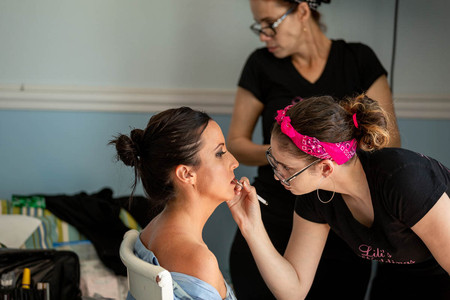 makeup artist working with bride onsite at the venue