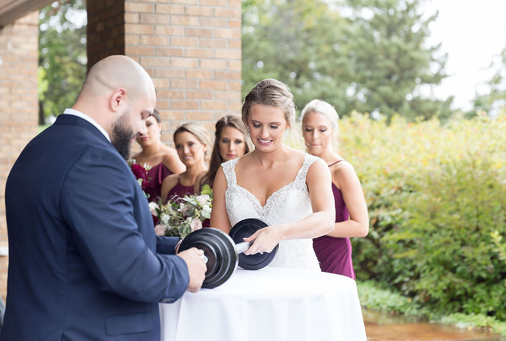 Bride and Groom assemble barbell together as a unity ceremony.