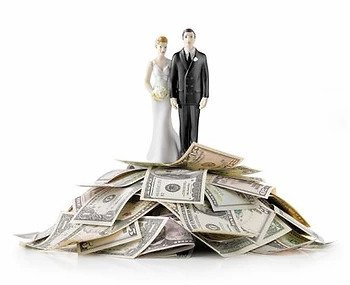 bride and groom cake topper on top of a pile of money