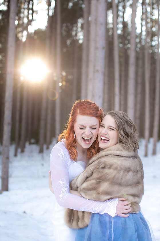 Two brides laughing during sunset golden hour at Pinewood Weddings and Events in Cambridge, Minnesota