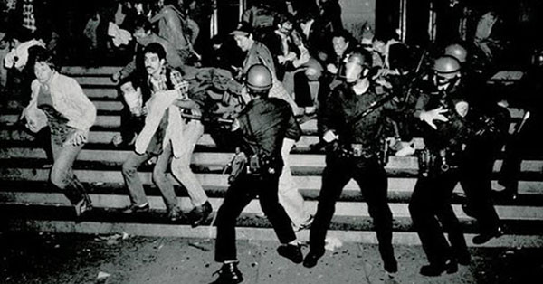 Police in riot gear advancing toward LGBTQ and allied activists in the Stonewall Riots of 1969.