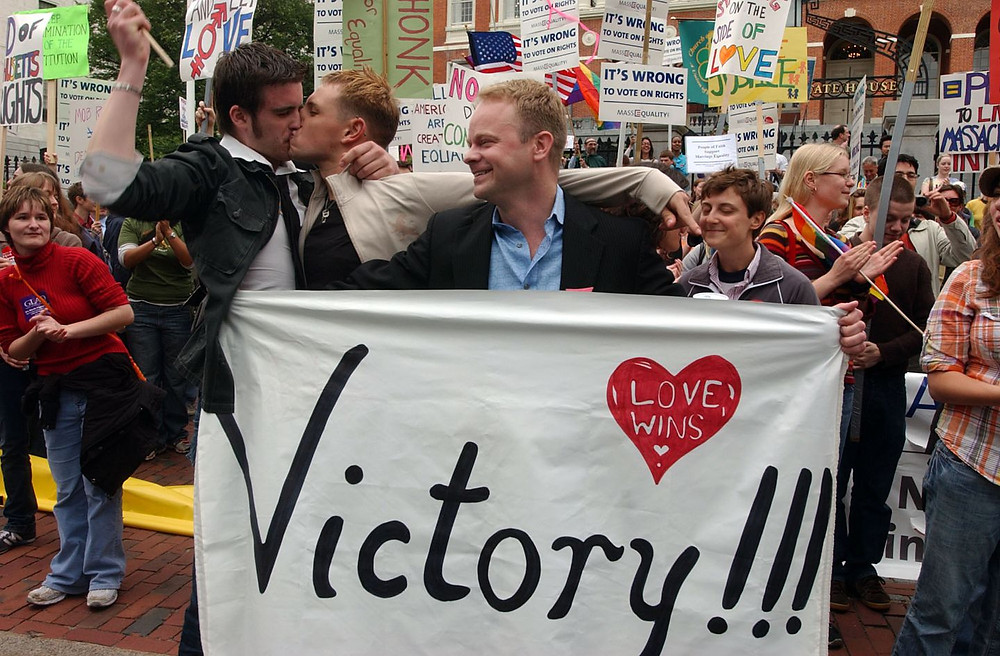 """Man holding sign reading """"Victory!!! Love Wins"""" as two men kiss behind him celebrating Massachusetts history making decision to legalize same-sex marriage."""