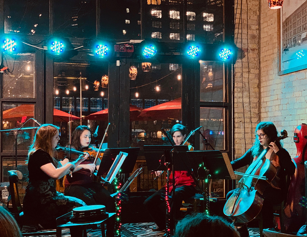 string quartet performing live music at a holiday party