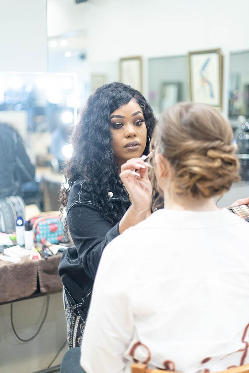 makeup artist applying makeup on bride in a salon