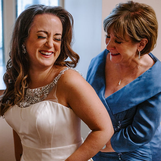 Mother of the bride helping her daughter into her wedding dress at Our Lady of Lourdes Catholic Church in Minneapolis, Minnesota