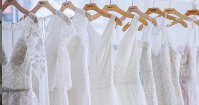 Wedding dresses on hangers in a consignment store.