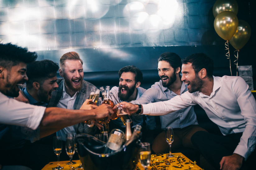 Groom and groomsmen toasting with beer and whiskey at bachelor party.