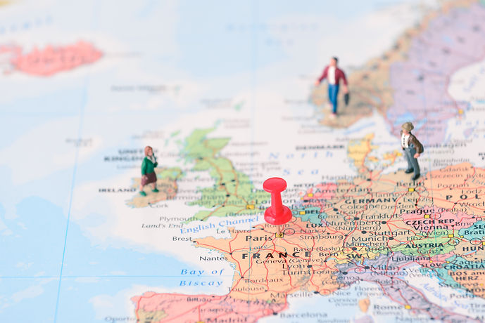 Pinned on map of Paris in France and miniature travelers.jpg
