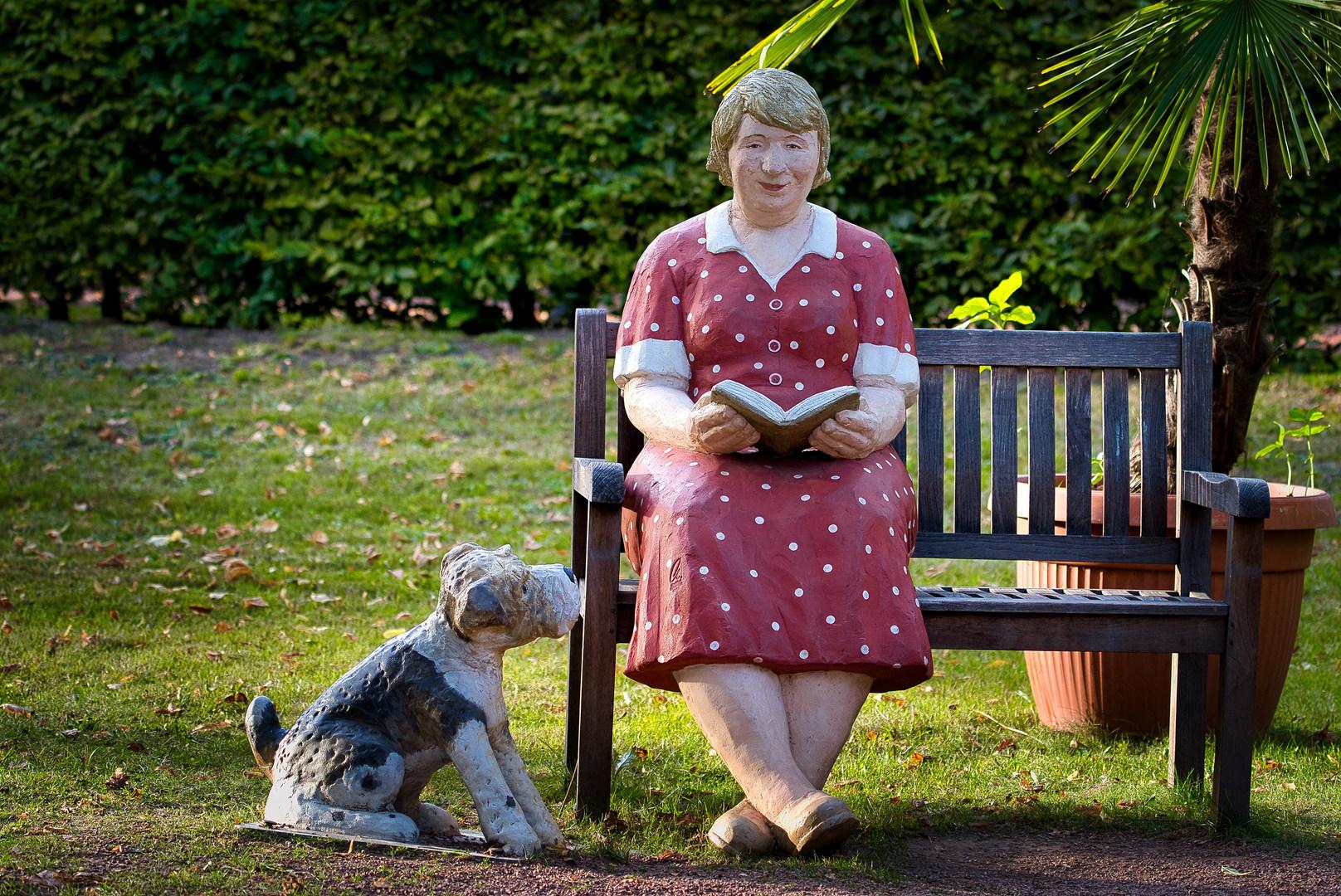 Die lesende Frau mit Hund auf einer Bank im Park