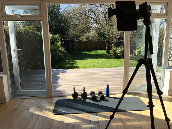 a tripod with an ipad overlooking a gym mat and free weights in a home conservatory