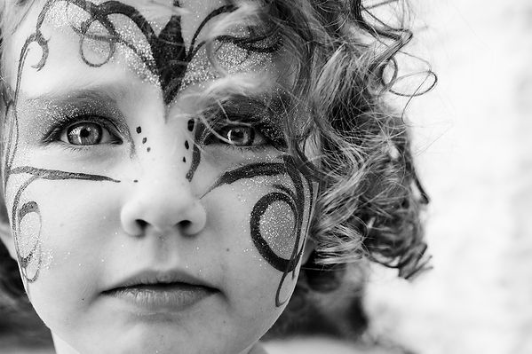 Child with painted face at Festival Number 6, Portmerion. Image by Wesley Storey