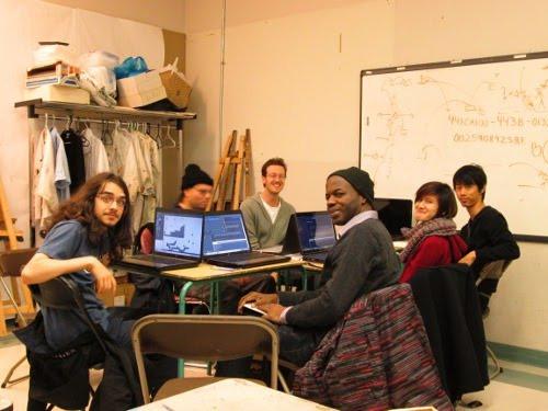 Photo montrant cinq jeunes et l'animateur de l'atelier sont assis autour d'une table avec des ordinateurs.
