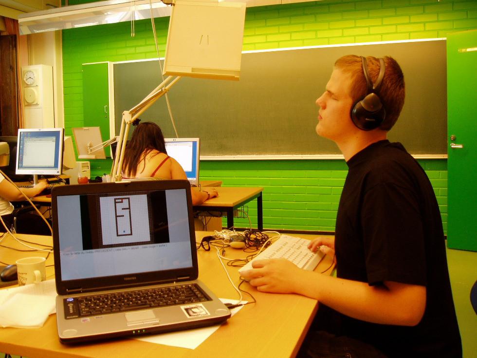 Photo montrant un joueur aveugle en train de tester un jeu de labyrinthe sonore.