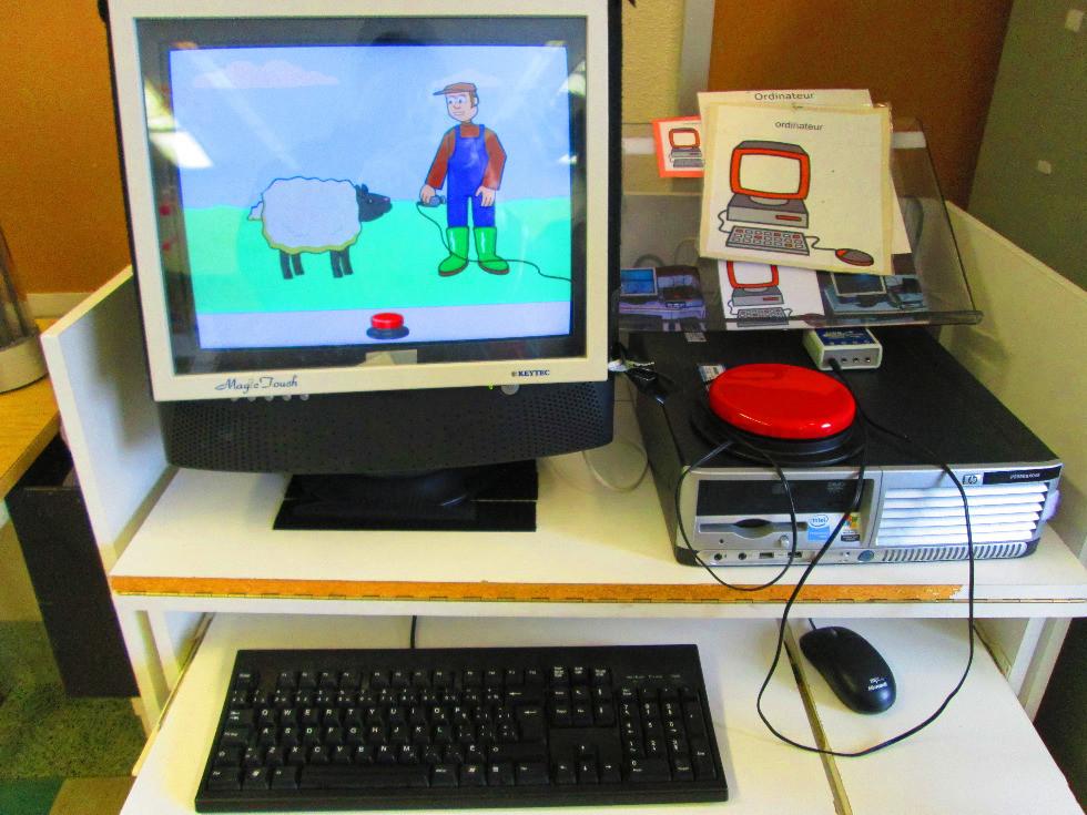 Photo montrant l'ordinateur de la classe avec un gros contacteur rouge.