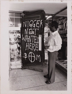 05 Eric Huntley (showing racist graffiti on the Bookshop's door). c1970s.  Huntley Archives at Londo