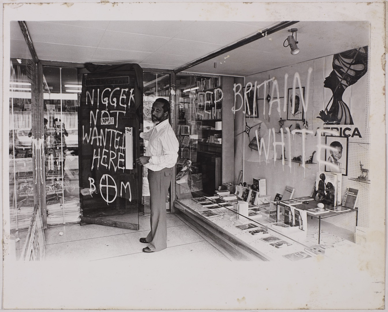 06 Eric Huntley (showing racist graffiti on the Bookshop's door). c1970s. Huntley Archives at London