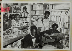17 L to R - Eric Huntley _ Keith Waite (playing flute) at Bookshop event. c1970s. Huntley Archives a